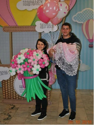 Счастливые муж и жена с цветами из шариков